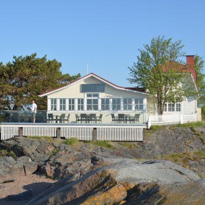 En gammal vit trävilla med rött tak vid havet, på uteserveringen står en man.