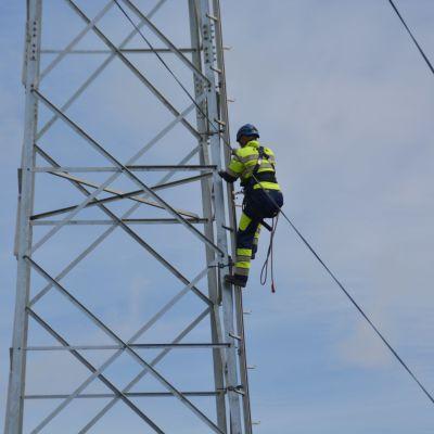 Elektriker klättrar i en högspänningsstolpe