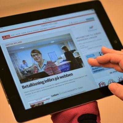 Hand som scrollar på pekplatta där Västra Nyland syns på skärmen.