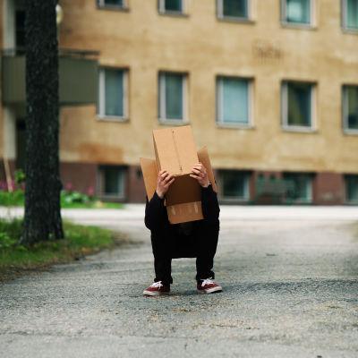 Ihminen kyykkii pahvilaatikko päässään kerrostalolähiössä.