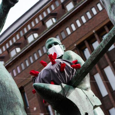 Kolmen sepän patsaan hahmoit takovat koronavirusta 31.3.2020.