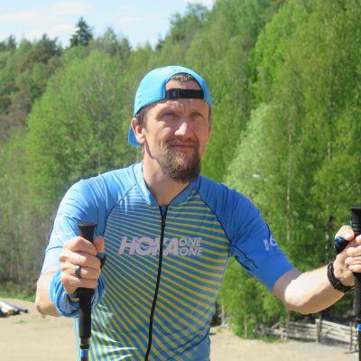 Ville Maksimainen juoksee sauvat kädessä laskettelurinnettä ylös
