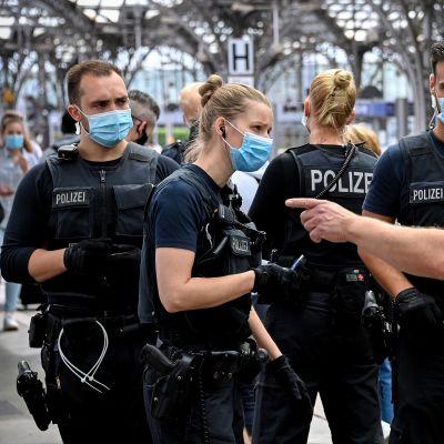 Poliser stoppar en person i Köln som brutit mot coronareglerna.