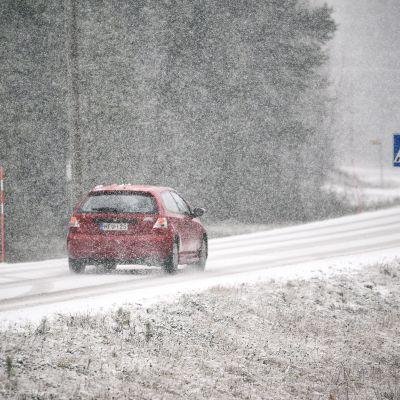 auto tiellä ja lunta sataa