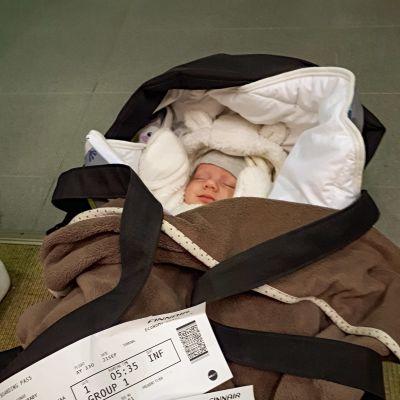En baby i sin vagn. Ovanpå vagnen ligger två flygbiljetter.