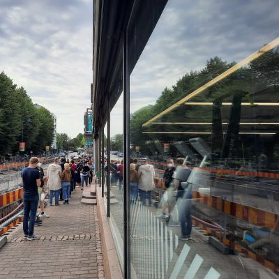 Ihmisiä jonossa koronarokotetta varten Kotkan Pasaatin kauppakeskuksen edessä jalkakäytävällä.