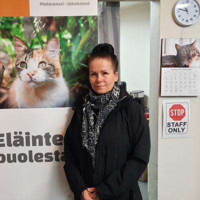 Kvinna som står framför en vägg med en vild av en katt.