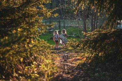 Kaksi lasta metsäretkellä. Lapset kuvattu takaapäin.