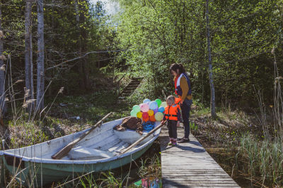 Äiti ja lapsi lähdössä veneretkelle. Mukana paljon ilmapalloja.