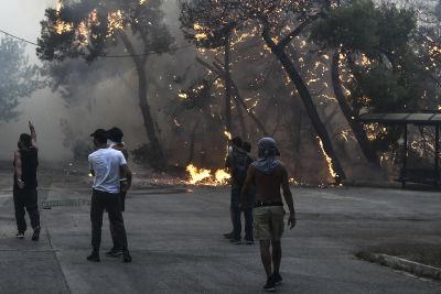 Människor går vid en skogsbrand på den grekiska ön Euboia.