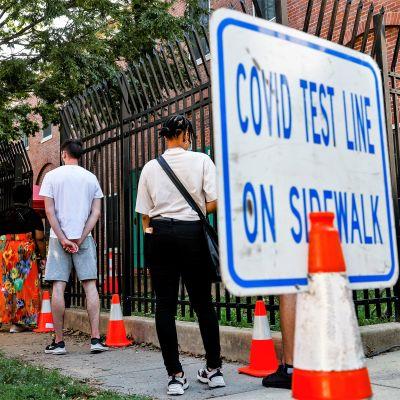 """Joukko ihmisiä jonottaa koronavirustestiin jalkakäytävällä. Etualalla näkyy liikennekartioon liitetty kyltti, jossa lukee """"COVID-testauslinja jalkakäytävällä"""""""