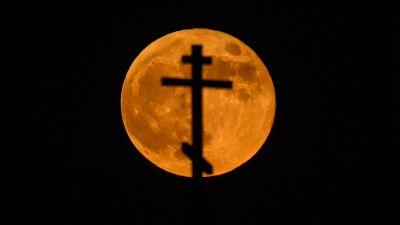 En blodröd måne syns bakom ett ortodoxt kors.