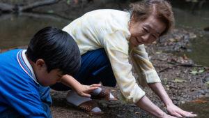 Mormor (Yuh-Jung Youn) och barnbarnet David (Alan S. Kim) står vid en flodstrand och doppar händerna i vattnet.
