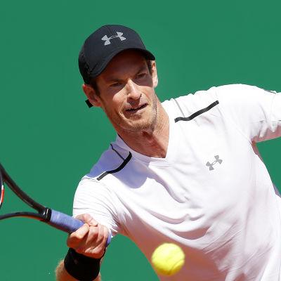 Vitklädde tennisspelaren Andy Murray slår en tennisboll.