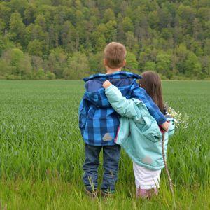 En pojke håller om en flicka och blickar ut mot en äng