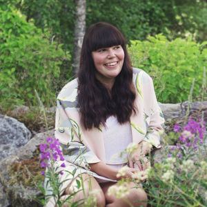 Michaela Finne sitter vid ett stenröse. I förgrunden syns rosa sommarblommor.