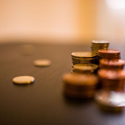 Högar med mynt på ett bord.