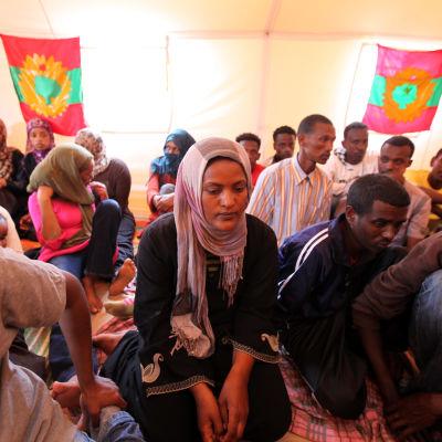 Flyktingar från Oromo i Libyen sörjer drunknade flyktingar. I bakgrunden syns rebellflaggan för Oromos Befrielsefront