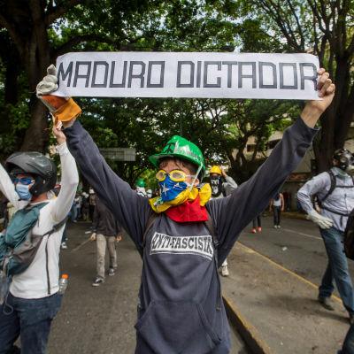 """""""Maduro är diktator"""" står det på den här unga demonstrantens banderoll. 1.5.2017"""