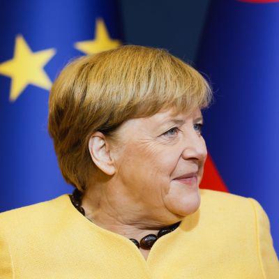 En bild på Tysklands förbundskansler Angela Merkel. Hennes blick är riktad bort från kameran. I bakgrunden ser man EU:s flagga.