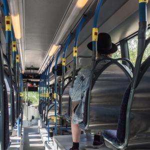 En person med hatt inne i en buss från Esbo till Helsingfors.