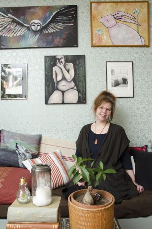 En kvinna som sitter på en soffa. Bakom hennes syns tavlor hon själv målat eller fotat. De föreställer djur och kvinnokroppen.