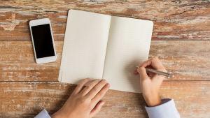 Två händer fotograferade uppifrån. Under dem finns ett bord. Ena handen håller i en penna och ska precis börja skriva något i ett häfte som ligger på bordet. Bredvid häftet ligger en smarttelefon.