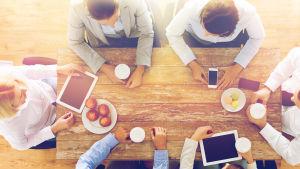 En bild på några personer runt ett bord tagen uppifrån.