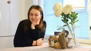 En ung kvinna sitter vid ett köksbord och lutar kinden mot den ena handen.