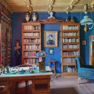 Kuva työhuoneesta, työpöydällä pieniä veistoksia, taustalla kirjahylly, kuvan oikeassa laidassa näkyy divaania