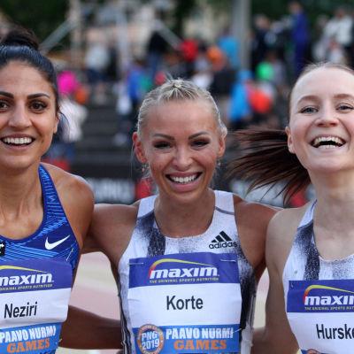 Nooralotta Neziri, Annimari Korte och Reetta Hurske håller om varandra och ler.