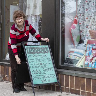 Vappu Ihalainen asettelee mainoskylttiä kauppansa edessä.