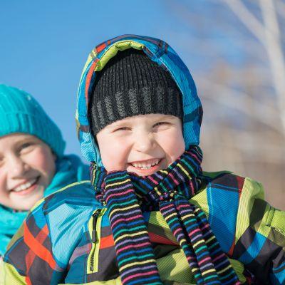 En pojke och en flicka i vinterkläder skrattar mot kameran