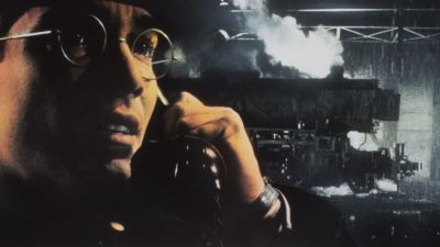 Närbild på en glasögonprydd Jean-Marc Barr stående framför ett tåg i filmen Europa.