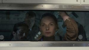 Miranda (Rebecca Ferguson) står och ser ut genom ett fönster.