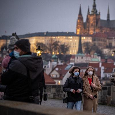 Kaksi naista kävelee hengityssuojaimet kasvoilla sillalla Prahassa.