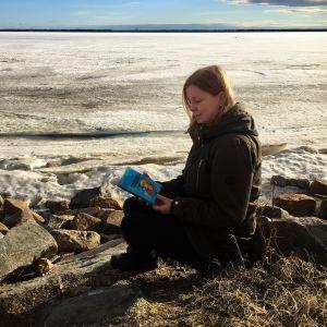 Hannan kirjokansi -blogin pitäjä lukee kirjaa Oritkarin talvisella rannalla.