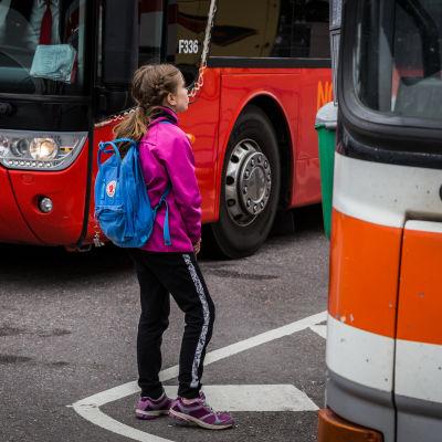 Flicka väntar på buss