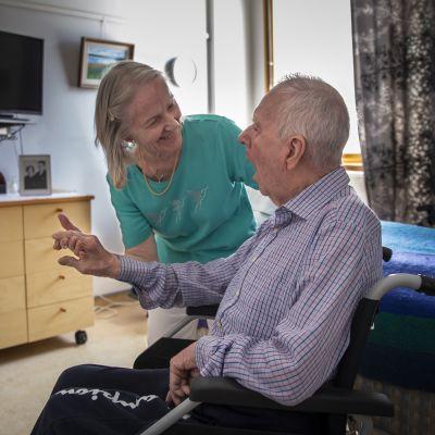 Irmeli och Heikki Laajanen på ett vårdhem. Heikki sitter i rullstol och Irmeli tittar på honom och håller handen på hans rygg.