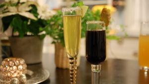 Två champagneglas med frosting av socker, ett med en ljusgul drink och ett med en mörkbrun drink. Den ena drinken är garnerad med en äppelskiva och den andra med en skiva ingefära.