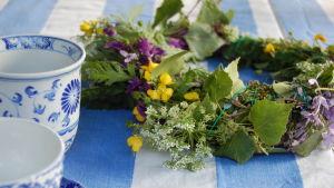 En blomsterkrans på ett bord med två koppar.