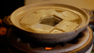 Tofubitar i en skål med hett vatten.