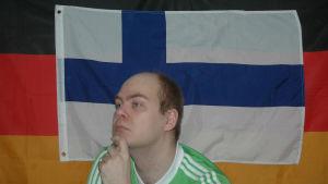 tekijän omakuva, suomen ja saksan liput taustalla