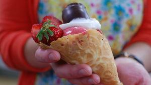 En hand som håller ett hemlagat glassrån fyllt med jordgubbssorbet, grädde, jordgubbar och choklad.
