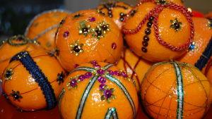Mandariner som dekorerats med paljetter och sidenband i olika färger och mönster.