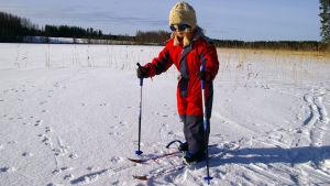 Pikkutyttö hiihtää järven jäällä