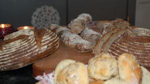 Ett skärbräde med hembakt bröd i olika utformning, några ljusa semlor med frön på, några grovt tvinnade baguetter och limpor som snittats för vackra mönster.