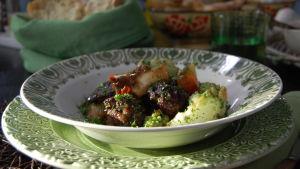En portion lammgryta med mos och romanesco garnerad med finklippt persilja. Portionen är serverad i en djup tallrik som är vit med en grön bård.