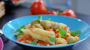 En portion penne pasta med tomatsås, garnerad med oliver och färska örter. Portionen är serverad på ett himmelsblått fat.