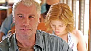 John Travolta katsoo eteenpäin, takana ilmeisesti bussissa istuu alaspäin katsova Scarlett Johansson.